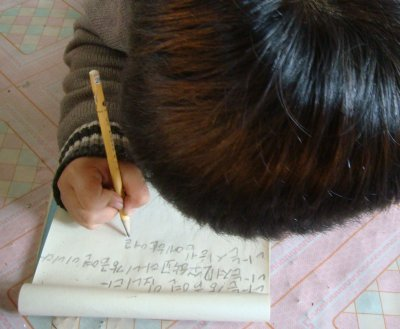 Refugee child in one of LFNKR's shelters writing to foster parent in Japan.