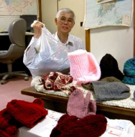 LFNKR's Kato displays some of the knitted goods donated from the US