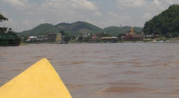 In the distance, refugees can see the Golden Buddha from midriver